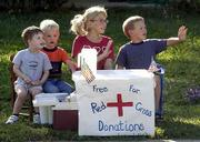 These children are doing their part to help victims of Tueday's terrorist attacks by trading lemonade for donations along Kasold Drive. From left are Jacob Russell, 3; Cole Wolff, 3; Kajsa Mullenix, 9; and Kjell Mullenix, 6. Kajsa said she planned to have the stand open this afternoon, offering hot cocoa and coffee.