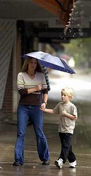 Despite having an umbrella, Tracie Mann, left, and Dante Colombo, 6, sidestep an awning's runoff to escape the rain. Lawrence received 0.49 inch of rain from midnight Monday through Tuesday evening, bringing the year's total precipitation to 35.40 inches. For today's weather, please see 10B.