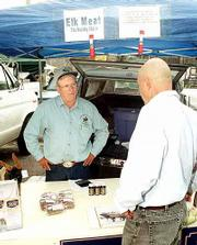 Rocky Hills Elk Ranch owner Charles Edmonds, left, talks about his elk herd with customer Bob Anderson, Towanda. Edmonds packs his pickup truck full of coolers containing ground elk, elk burgers, elk steak and elk sausage each Saturday and makes the 24-mile journey to the Lawrence Farmers Market.