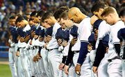 MEMBERS OF THE NEW YORK YANKEES bow their heads during the national anthem on Tuesday in Chicago. The Yankees beat the White Sox, 11-3.