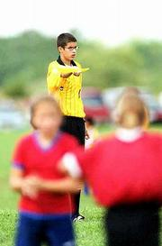 Andrew Fyler, 15, indicates a goal kick during an under-12 girls soccer game at Youth Sports Inc. fields in southwest Lawrence. Fyler, who attends West Junior High School, is in his first year of officiating soccer.