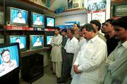 Pakistanis watch President Gen. Pervez Musharraf address the nation in the port town of Karachi. Musharraf said Wednesday that U.S. plans against suspected terrorist Osama bin Laden were not yet completed but reassured his nation there was no intention to target Islam or the people of Afghanistan.