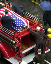 A Franciscan priest touches the flag-draped casket of New York City firefighter William Henry, who was killed in the World Trade Center attack, as it rests atop a fire truck after the funeral Mass at the Church of Saint Francis of Assisi. Henry's funeral Thursday was one of eight for fallen New York firefighters; funerals for another two firefighters killed in the attack were Friday.