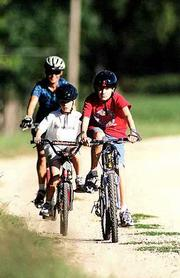 Philip Gilreath, 13, leads his younger brother Stuart Gilreath, 9, and mother Mitzi Gilreath around a bend on the Kansas River levee bike path at Riverfront Park in North Lawrence. Mitzi Gilreath said she liked to bring her family to Riverfront Park to ride bikes and jog, and did so often, because it was fairly flat and level and easier for her sons to navigate than other paths in Lawrence.