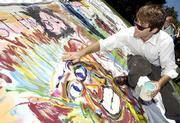 Expressing themselves through art, Kansas University students like senior Andrew Vratil, Overland Park, work on a collaborative memorial in reflection of the terrorist attacks on the East Coast. Vratil was among those Friday at the Art and Design Building who were painting a 30-foot canvas. Organizer and junior Lisa Thalhammer, St. Louis, said she hoped to display the painting in a campus gallery.