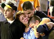 Carol Gies, center, wife of missing firefighter Ronnie Gies, leans on son Ronnie, left, and she is comforted by sons Bobbie, right, and Tommy. They were attending ceremonies for victims at the World Trade Center on Friday night at Shea Stadium in New York.