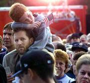 Scott Miller holds his son Jeffrey, 5, as they wait to pass through a security check point at Shea Stadium before a game between the New York Mets and the Atlanta Braves. The event Friday was the first professional baseball game in New York since the Sept. 11 terrorist attacks. Security at stadiums across the country is expected to be heightened this weekend in the wake of the attacks.
