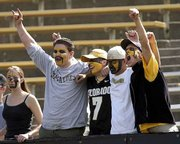 "COLORADO FANS enthusiastically sing ""God Bless America"" before kickoff Saturday in Boulder, Colo."