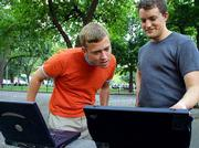 Anthony Townsend, 27, left, and Terry Schmidt, 25, use wireless Internet from their laptop computers in a New York park. Schmidt belongs to a budding group of digital activists in North America and Europe who are providing the public with pockets of free wireless Internet access.