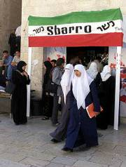 Palestinian students walk under a replica of a Sbarro pizza restaurant sign during the opening of an exhibition at Al Najah University in the West Bank town of Nablus. The exhibit opened Sunday to commemorate one year since renewed violence broke out between Israelis and the Palestinians.