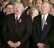 "Rep. Tom DeLay, R-Tex., House majority whip, left at rear, House Speaker Dennis Hastert, R-Ill., and Rep. Richard Gephardt, House minority leader, sing ""God Bless America"" during a prayer vigil in the rotunda of the Capitol. Across America, the song has been sung by millions of people at every type of event."