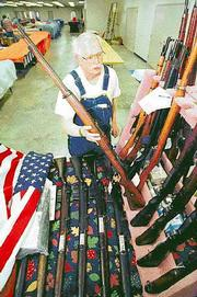Terril Huntley, Muscotah, looks over some of the World War I and World War II rifles in his collection in preparation for a gun show last year at the Douglas County 4-H Fairgrounds. Douglas County Commissioners are considering restrictions that require all vendors to perform background checks on gun buyers at gun shows.