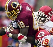 Washington Redskins running back Stephen Davis (48) carries the ball with Kansas City Chiefs defensive end Rich Owen, top right, and linebacker Donnie Edwards (59) hanging on during the second half of their game Sunday in Landover, Md. The Chiefs beat the Redskins, 45-13.