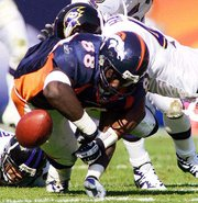 Denver tight end Desmond Clark (88) fumbles after being tackled by Baltimore's Corey Harris, right, during the second quarter Sunday in Denver. The Ravens won, 20-13.