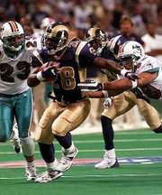 St. Louis running back Marshall Faulk, center, is pursued by Miami's Patrick Surtain (23) and Jason Taylor, right, in the third quarter of Sunday's game in St. Louis. Faulk scored three touchdowns in the Rams' 42-10 win.