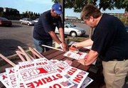 Minnesota Association of Professional Employees members Richard Allison, left, and Marty Kumm put together strike signs. Two state unions decided Sunday to hit the picket lines early this morning.