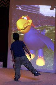 A young visitor does the Hokey Pokey in front of the Kansas University Cyber Jay at Murphy Hall. He was one of the more than 20,000 people who turned out Saturday for KU's open house.