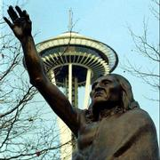 The Space Needle looms over a statue of Chief Seattle, who is buried at the Port Madison Indian Reservation on the Kitsap Peninsula. A memorial stating his role in the city's development greets visitors at the Suquamish Memorial Cemetery.