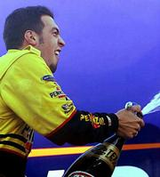 SAM HORNISH JR. sprays champagne while celebrating his Chevy 500 victory on Saturday at Texas Motor Speedway in Fort Worth, Texas. Hornish overtook Scott Sharp feet from the finish line for the closest 1-2-3 finish in IRL history.