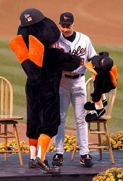 Baltimore's Cal Ripken gets a hug from the Orioles' mascot prior to playing the final game of his career Saturday night at Camden Yards in Baltimore.