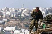 An Israeli soldier climbs down from a tank parked in a new position on a hilltop overlooking the West Bank town of Hebron. As the U.S. launched a military strike Sunday on Afghanistan, three people were killed in Israeli-Palestinian fighting.