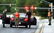 Soldiers inspect a car at an entrance to Fort Bragg in Fayetteville, N.C. Officials at Fort Bragg say they are at a heightened state of security due to the start of attacks on Afghanistan.
