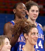 Kansas BASKETBALL sophomore Keila Beachem styles senior Kristin Geoffroy's hair while freshman Valerie Migicovsky watches the camera. The Jayhawks gathered for a team photo during media day Wednesday at Allen Fieldhouse.