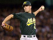 Oakland's Mark Mulder delivers against the Yankees. Mulder held New York to one run in 623 innings as the Athletics defeated the Yankees, 5-3, in the opening game of their playoff series Wednesday night in New York.