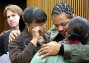 Anthony Michael Green gets a hug from his sister, Sharon Pascol, right, and friend Patricia Everson after the rape conviction against him was vacated by a Cuyahoga County judge in Cleveland. DNA testing of 13-year-old evidence proved Green could not have committed the crime. In the left background Thursday is attorney Barry Scheck, who helped prove Green's innocence.