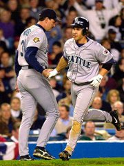 Seattle's Bret Boone, right, is congratulated by third base coach Dave Myers after his homer. The Mariners beat the Yankees on Saturday at New York.