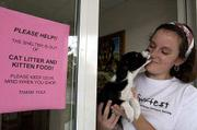 A sign reminding people to think of the Lawrence Humane Society when they shop helps to spread the word about needed supplies for the shelter. Amy Tramill, the organization's education coordinator, held a mixed-breed puppy on Thursday at the shelter.