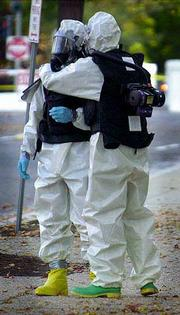 Two hazardous materials investigators embrace as they prepare to enter the Dirksen Senate Office Building in Washington, D.C. Workers continued Sunday to sweep buildings on Capitol Hill for anthrax. Meanwhile, a District of Columbia postal worker became the third person in the nation to come down with the most serious form of the disease.