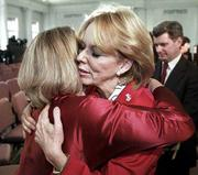 American Red Cross President Bernadine Healy is embraced by a Red Cross worker, left, after Healy announced her resignation Friday to Red Cross employees at their Washington headquarters.