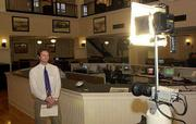Lawrence Journal World writer Tim Carpenter goes live on local TV from the paper's newsroom. The newspaper and local cable TV operate a combined news operation.