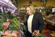 Karen Pagel-Meiners, Lawrence, uses a list to shop from that identifies available produce supplied by local people at the Community Mercantile, Ninth and Iowa streets. Saturday the store featured an event called Local Food to Local People to promote area growers products.