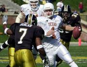 Texas quarterback Chris Simms, center, scrambles as Missouri's Antoine Duncan (7) and Dan Davis, right, close in. Texas won, 35-16, on Saturday at Columbia, Mo.