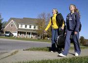 Headed home for the weekend with orchestra instruments and bookbags in tow are Southwest Junior High students Aarynne Struble, ninth grade, left, and Adrienne Struble, seventh grade. The sisters walked along Turnberry Drive Friday in southwest Lawrence, an area of town experiencing a growth explosion.