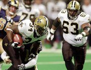 New Orleans running back Ricky Williams (34) is wrapped up by St. Louis' Adam Archuleta during the third quarter of Sunday's game. Also pictured is New Orleans' Wally Williams (63). The Saints won, 34-31.