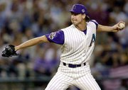 "Arizona&squot;s Randy Johnson delivers a pitch during the first inning. ""The Big Unit"" threw a complete-game shutout against New York on Sunday in Phoenix. The Diamondbacks lead the World Series 2-0."