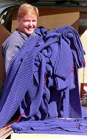 Ray Ettinger of Independence, Mo., holds a small portion of the scarf he knitted that is listed in the Guinness Book of World Records as the world's longest knitted scarf. The scarf, begun in 1995, is 7 inches wide by 3,523 feet long. It fills two large boxes in the back of his van.