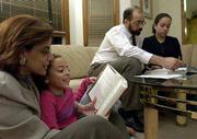 Family time for Maggie Khater and her husband Moussa Elbayoumy is typical of many Muslim families in America; it often centers around their children, Nora, 7, and Sarah, 13. Monday evening, Maggie read a Harry Potter story with Nora while Moussa and Sarah tackled Algebra II homework. in their Lawrence home.