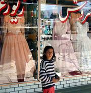 A young girl passes the dresses on display in Kabul, Afghanistan. Shopkeepers in the capital who sold western-style wedding dresses welcomed the departure of the hardline Taliban Islamic rulers, who opposed western dress and required women to wear burqas.