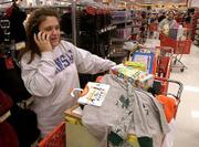 "In a phone call to her husband, Shelley Dohle, Eudora, reports on the items she has purchased at SuperTarget, 3201 Iowa. Dohle was at Kmart when it opened at 5 a.m. Friday and then hit SuperTarget and Kohl&squot;s on what is traditionally the busiest shopping day of the year. ""I&squot;m done,"" remarked Dohle. ""I&squot;m going to go home and go to sleep now."""