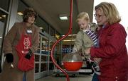 The Salvation Army hopes to raise $150,000 this holiday season to support its homeless shelter, feeding programs and youth basketball for the next year. Bell-ringer Norrie Iams, left, works Friday outside the Kmart Store, 3106 Iowa, as Peyton Durand, 2, drops money in the red kettle with help from his mother, Eva Durand, Baldwin.