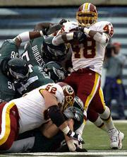 Washington kick returner Michael Bates (20) gets upended by Philadelphia linebacker Barry Gardner (52). The Redskins upended the Eagles, 13-3, on Sunday in Philadelphia.