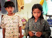 "Thirteen-year old twins Luther, left, and Johnny Htoo once led the Myanmar guerrilla group ""God&squot;s Army."" The Thai government has requested that the United States consider the twins and their family for resettlement, but the twins say they don&squot;t want to go."