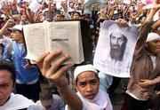 A protester holds up the Quran and a picture of terrorist suspect Osama bin Laden during an anti-U.S. protest in Jakarta, Indonesia. The rise of Islamic militancy in the island nation is a threat both Indonesia's government and to Western countries.