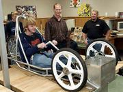 With assistance from local racing pro Rob Wendland, right, students in technology classes at Free State High School are building an electric race car. Sophomore Andy Alldredge, left, sat in the driver's seat Tuesday as instructor Troy Damman, center, and Wendland talked about the car's construction.