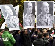 Afghan royalists hold up posters of King Mohammad Zaher Shah during a rally in Koenigswinter, near Bonn, Germany. Afghan factions opened talks Tuesday on how to share power and secure peace once the Taliban are defeated in Afghanistan.