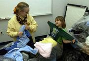 EVE COFER, left, director-coordinator of Douglas County ECKAN, and Cara Burrous, a member of an adopted family, sort through donated clothes. ECKAN is looking for more volunteers to help set up and distribute donated items to adopted families.